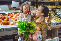 Family in the supermarket. Beautiful young mom and her little daughter smiling and buying food stock photos