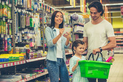 Family in the supermarket. Beautiful young parents and their cute little daughter are smiling while choosing school stationery in the supermarket. Mom is making royalty free stock image