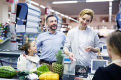 Family by supermarket checkout. Happy young customer with plastic-card looking at cashier by supermarket checkout Royalty Free Stock Image