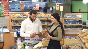 Family in supermarket, while choosing fresh bread in bakery department. Portrait of a young couple with a full trolley of products in the supermarket. Portrait stock video