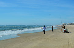 Family Surf Fishing Beach Ocean Water. A family out surf fishing with their lines cast out into the ocean waters on a bright blue sunny day at Emerald Isle, NC Stock Image