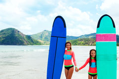 Family surfing. Mom with child are learning surfing together royalty free stock photo