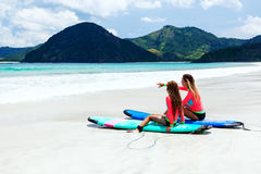 Family surfing. Mom with child are learning surfing together stock images