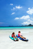 Family surfing. Mom with child are learning surfing together royalty free stock photography