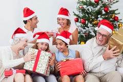 Family swapping christmas presents. Excited family swapping christmas presents on the couch Stock Photo