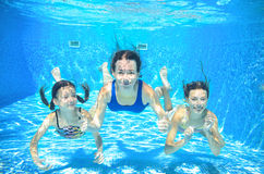 Family swim in pool underwater, happy active mother and children have fun in water, kids sport. On family vacation stock photo
