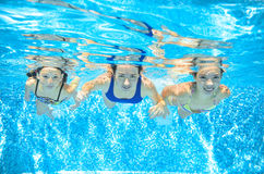 Family swim in pool underwater, mother and children have fun in water, Royalty Free Stock Photos