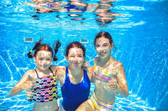 Family swim in pool underwater, mother and children have fun in water, Royalty Free Stock Photo
