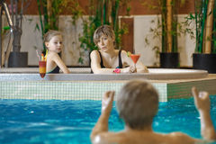 Family in swimming-pool. Happy attractive family relaxing by the pool Stock Photography