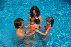 Family in swimming pool Royalty Free Stock Images