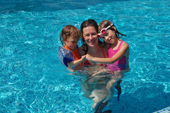 Family in swimming pool. Mother with children having fun in swimming pool Royalty Free Stock Images