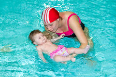 Family in the swimming pool. Young family with baby having fun in the swimming pool Royalty Free Stock Photo