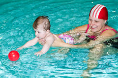 Family in the swimming pool. Young family with baby having fun in the swimming pool Stock Photos
