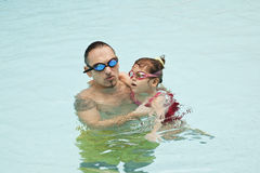 Family in swimming pool. Father and daughter in swimming pool Royalty Free Stock Image
