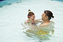 Family in swimming pool. Father and daughter in swimming pool Stock Image