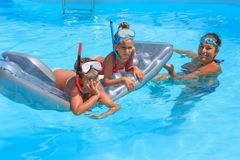 Family in the swimming pool. Mother and daughters in the swimming pool Stock Photography