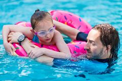 Family at swimming pool. Adorable girl with pink inflatable ring swimming in a pool with her father on summer vacation stock images