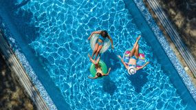 Family in swimming pool aerial drone view from above, happy mother and kids swim on inflatable ring donuts and have fun in water stock photography