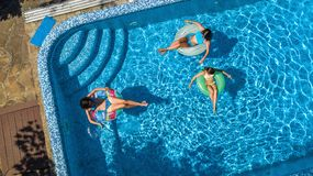 Family in swimming pool aerial drone view from above, happy mother and kids swim on inflatable ring donuts and have fun in water stock image