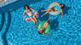 Family in swimming pool aerial drone view from above, happy mother and kids swim on inflatable ring donuts and have fun in water stock images