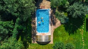 Family in swimming pool aerial drone view from above, happy mother and kids swim on inflatable ring donuts and have fun in water stock photos