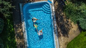 Family in swimming pool aerial drone view from above, happy mother and kids swim on inflatable ring donuts and have fun in water royalty free stock image