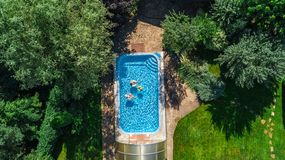Family in swimming pool aerial drone view from above, happy mother and kids swim on inflatable ring donuts and have fun in water stock photo