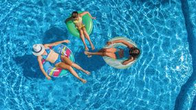Family in swimming pool aerial drone view from above, happy mother and kids swim on inflatable ring donuts and have fun in water. On family vacation, tropical stock photo