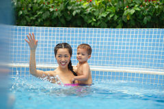 Family in the swimming pool. Asian family of two having fun in the swimming pool Stock Image