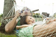 Family in swimming pool in a hammock blowing bubbles. Dad and daughter in a hammock blowing bubbles Royalty Free Stock Photos