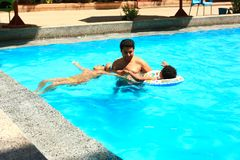 Family at swimming pool. Happy family swimming at pool Royalty Free Stock Image