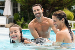 Family in swimming pool. Happy parents teaching their daughter how to swim. Happy girl learning to swim in swimming pool. Smiling family playing with daughter in Stock Photos