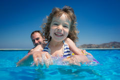 Family in swimming pool. Happy family playing in swimming pool. Summer vacations concept Stock Photography