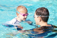 Family in the swimming pool. Happy son and his father spending time together in the swimming pool Royalty Free Stock Photos