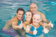 Family in swimming pool holding. Happy family with senior couple in swimming pool holding thumbs up Royalty Free Stock Photos
