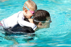 Family at swimming pool. Laughing cute son playing and swimming with his handsome young father at the pool Royalty Free Stock Photo