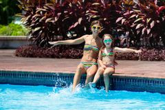 Family in swimming pool. Mother and child swim stock photo