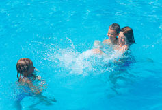 Family in the swimming pool. Mother with children to splash each other in the summer outdoor pool Stock Images