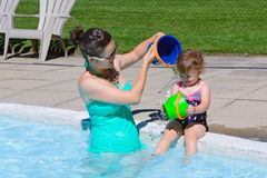 Family in swimming pool. Mother and daughter playing in water in swimming pool on sunny summer day Royalty Free Stock Photography