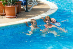Family in the swimming pool. Mother with her children in the summer outdoor pool Royalty Free Stock Photography