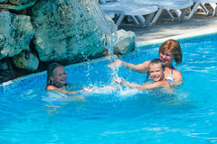Family in the swimming pool. Mother with her children in the summer outdoor pool Stock Photos