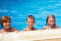 Family in the swimming pool. Mother with her children in the summer outdoor pool Royalty Free Stock Image