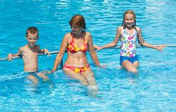 Family in the swimming pool. Royalty Free Stock Photography