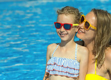 Family in swimming pool. Mother and her daughter having fun in swimming pool. Place for text Stock Photo