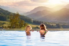 Family in swimming pool with mountain view. Kids play in outdoor infinity swimming pool of luxury spa alpine resort at sunset in Alps mountains. Spring or summer royalty free stock images