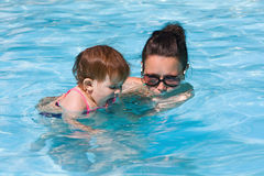 Family in swimming pool playing. Mother and daughter playing in water in swimming pool on sunny summer day, training to swim, healthy lifestyle Stock Image