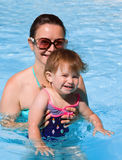Family in swimming pool playing. Mother and daughter playing in water in swimming pool on sunny summer day, training to swim, healthy lifestyle Royalty Free Stock Photos