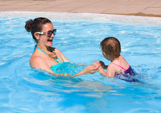 Family in swimming pool playing. Mother and daughter playing in water in swimming pool on sunny summer day, training to swim, healthy lifestyle Stock Photography