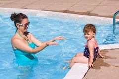 Family in swimming pool playing. Mother and daughter playing in water in swimming pool on sunny summer day, training to swim, healthy lifestyle Royalty Free Stock Images