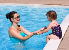 Family in swimming pool playing. Mother and daughter playing in water in swimming pool on sunny summer day, training to swim, healthy lifestyle Stock Photo